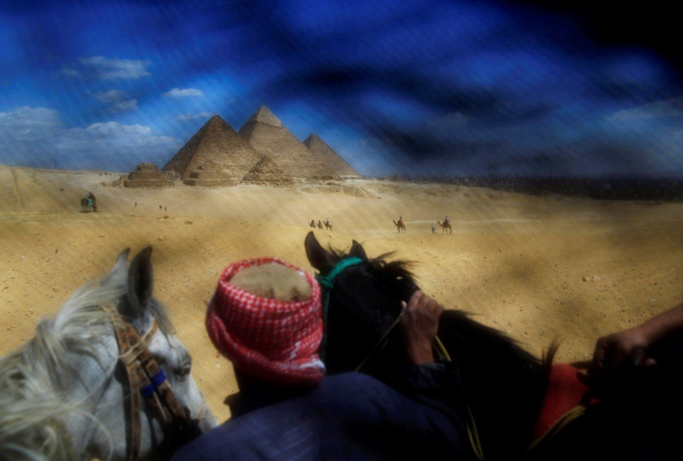 As seen through the veil: A man leading tourists riding horses at the historical site of the Giza Pyramids near Cairo.