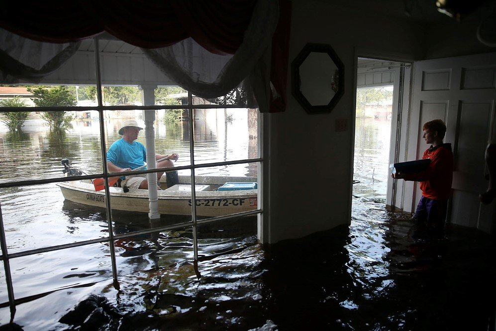 A man and a boy trying to move the left-over stuff during the record flooding in South Carolina – Oct. 9, 2015.
